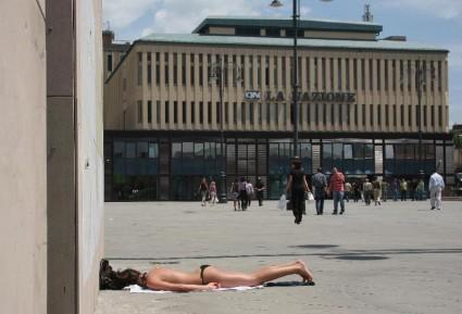Turista prende il sole in Piazza Annigoni